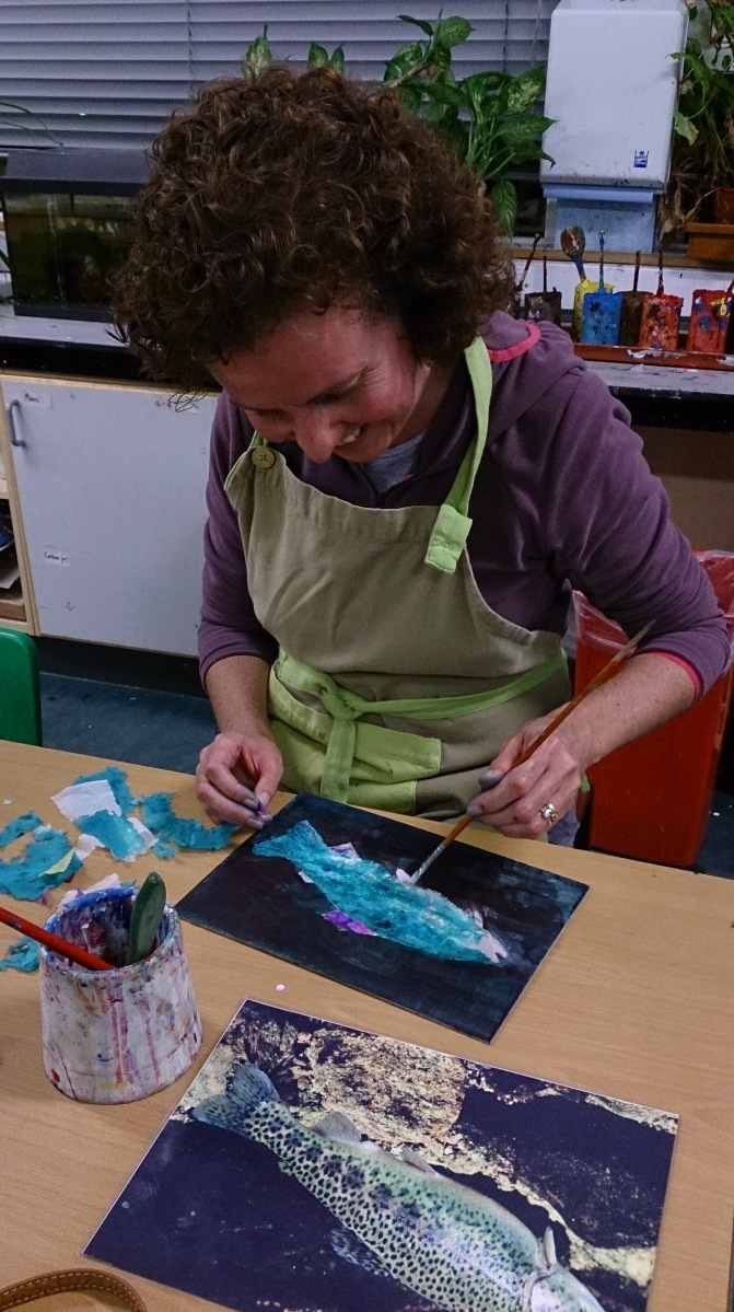 woman painting glue during a paper collage lesson