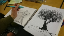 A person drawing two tree silhouettes