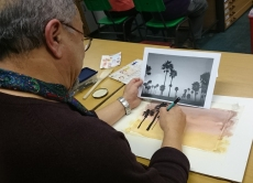 Man drawing palm tree silhouettes against a sunset