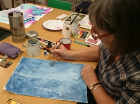 woman drawing onto a blue watercolour painting