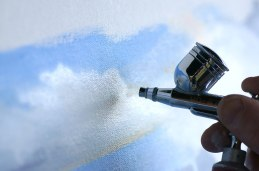 Airbrush being held by fingers near a canvas