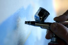 An airbrush bring held by fingers