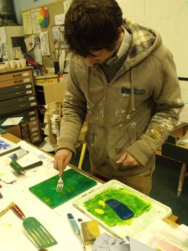 A man drawing fork across a painted surface
