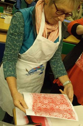 Woman looking at a red print of lace