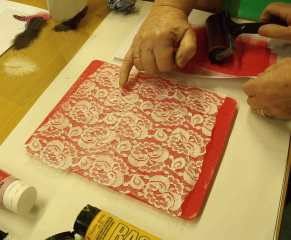 hand pointing at lace on coloured paint