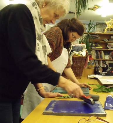 two women rolling ink out onto printing blocks