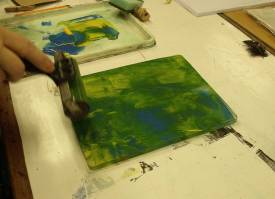 Hand rolling paint onto a gelli plate