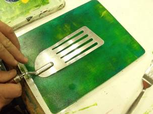 hands imprinting a fish slice into paint