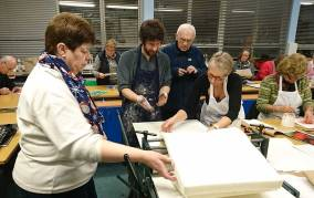 four people concentrating on placing a plate on the printing press