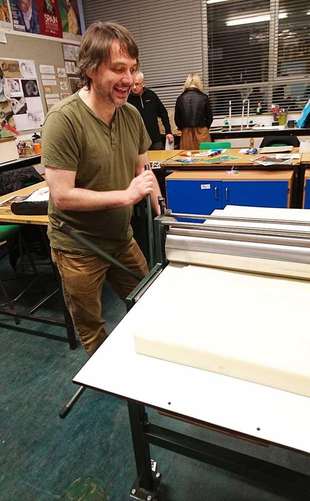 A man turning a printing press