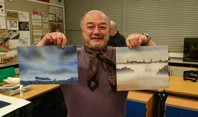 Man holding two landscape paintings