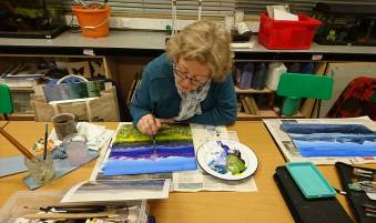Woman painting a brightly coloured landscape