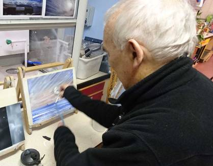 man airbrushing a landscape