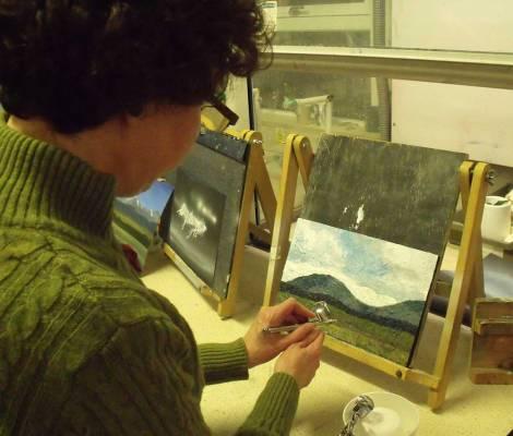 woman airbrushing a mountain landscape