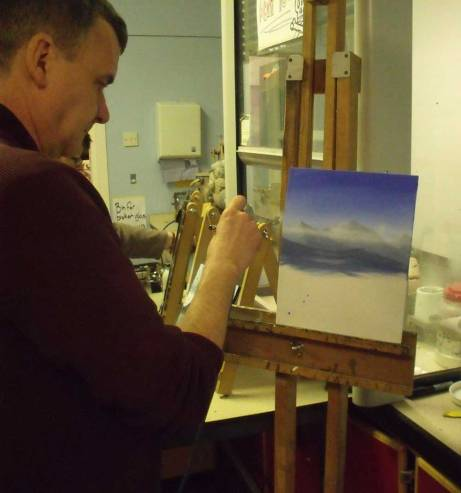 man airbrushing a mountain landscape