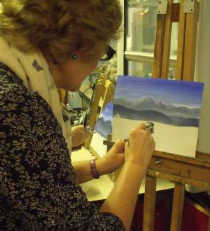 woman airbrushing a mountain landscape